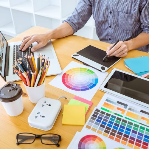 Young creative graphic designer working on project architectural drawing and color swatches, selection coloring on graphic chart with work tools and equipment.