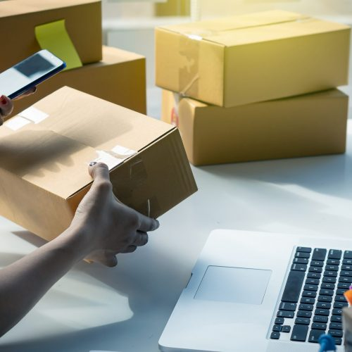 The right small business owner shoots a box of goods, ideas, startups and e-commerce. Asian business woman, online store manager, takes orders with laptop, packing box for delivery.